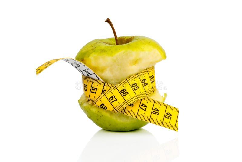Apple com fita de medição sobre foto de stock