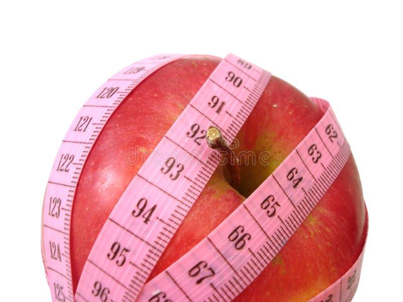 Apple Com Fita Métrica Cor-de-rosa Sobre O Fundo Branco (conceito De H Imagem De Stock