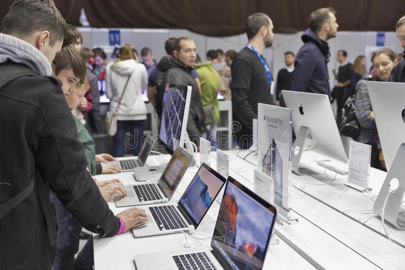 Apple company booth at CEE 2015, the largest electronics trade show in Ukraine. People visit Apple, an American multinational technology company booth during CEE stock photo