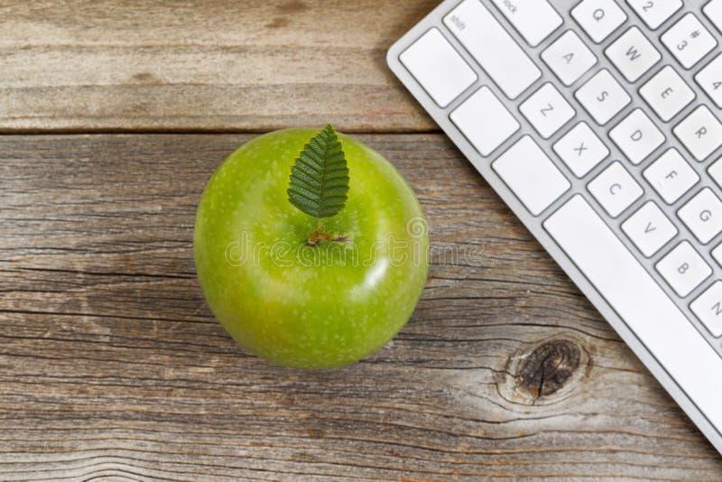 Apple con el teclado de ordenador para la escuela o la oficina en la madera rústica fotografía de archivo