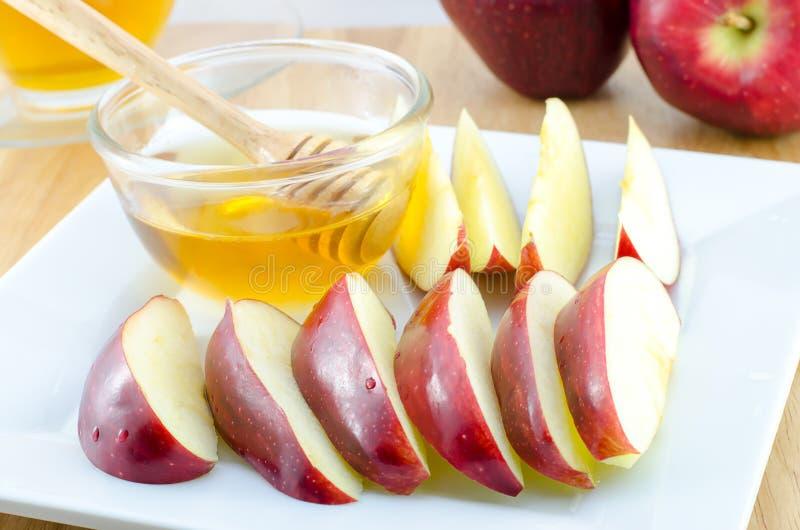 Apple con la miel en placa en la tabla de madera - Año Nuevo judío foto de archivo