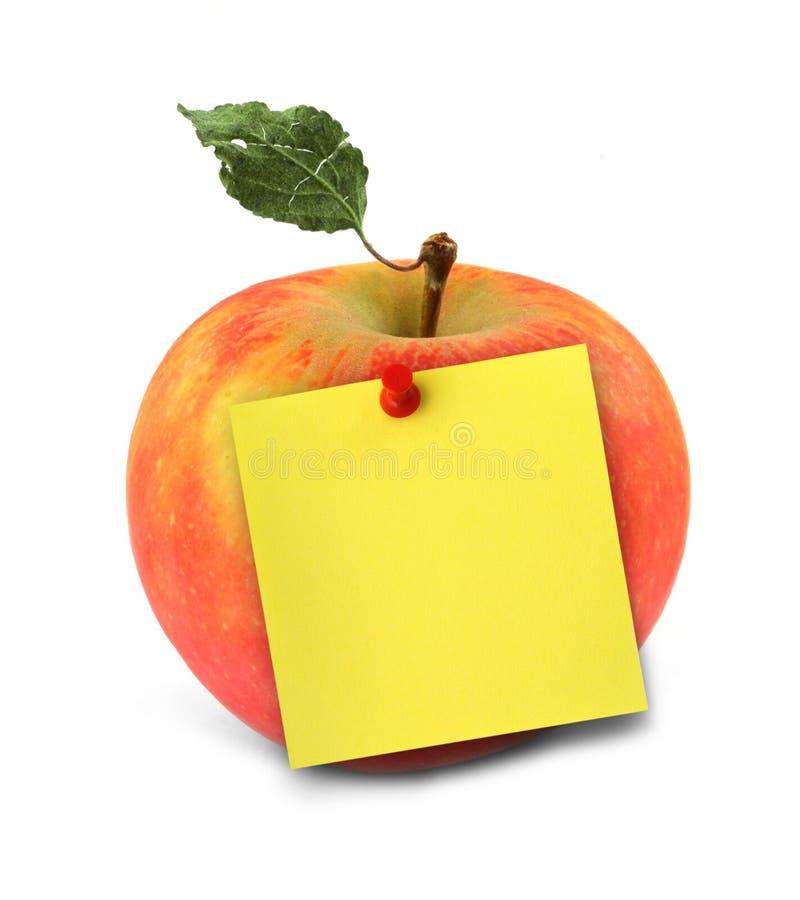 Apple con la nota amarilla fotografía de archivo libre de regalías