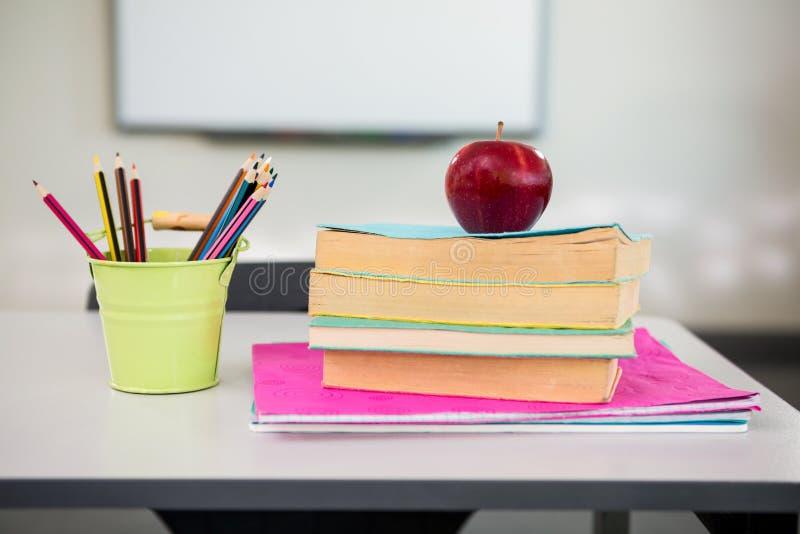 Apple con los libros y el organizador del escritorio en la tabla en sala de clase imagen de archivo