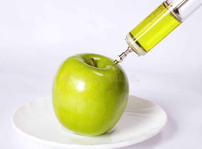 Apple con una siringa fotografia stock