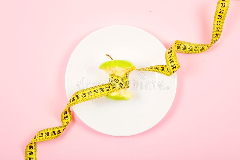 Apple core with measuring tape in place of the waist on a white plate on pink background. Diet, weigh loss, starvation, fitness. Concept stock photography
