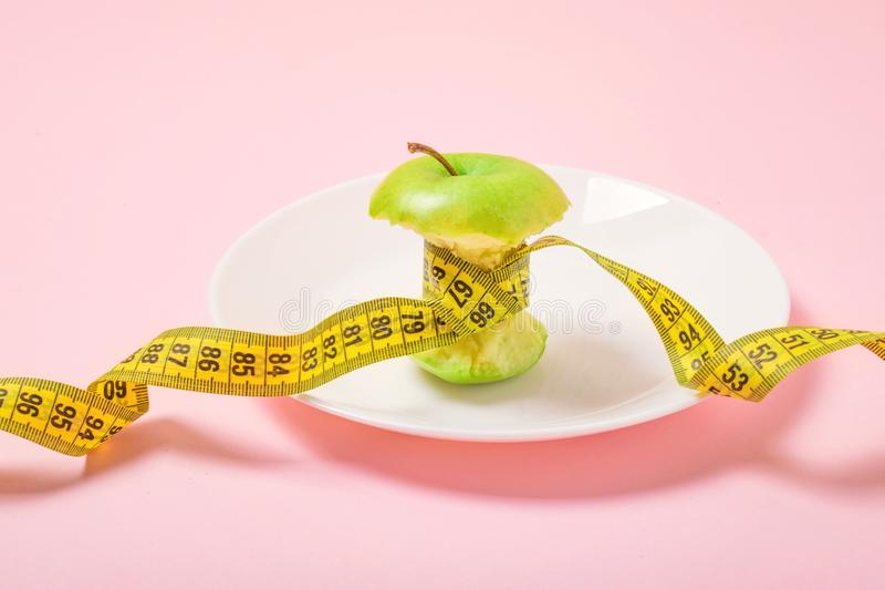 Apple core with measuring tape in place of the waist on a white plate on pink background. Diet, weigh loss, starvation, fitness. Concept stock photo