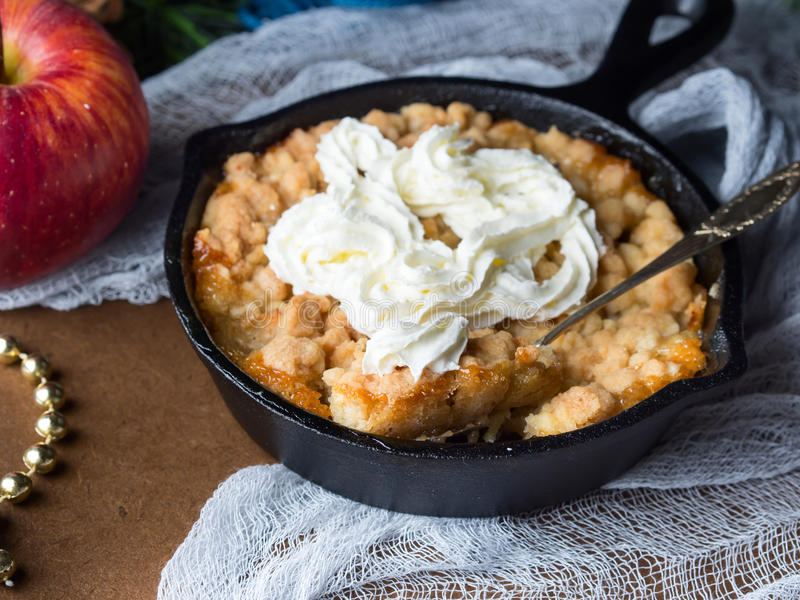 Apple crumble with cream in skillet. Closeup. Apple fruit crumble with cream as Christmas home made dessert. Festive treat served in cast iron skillet. Winter royalty free stock image