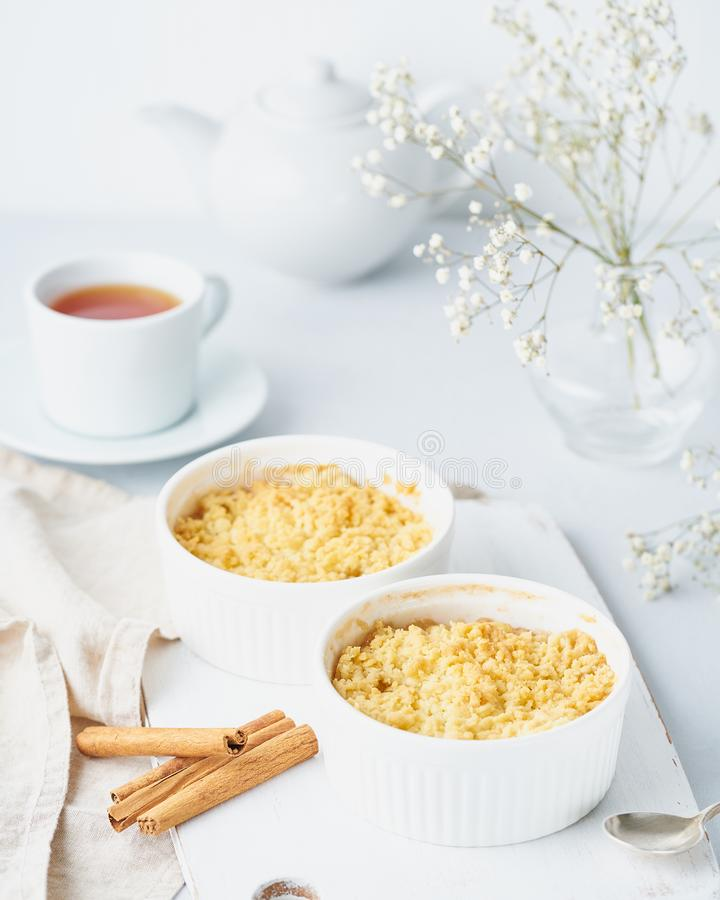 Apple crumble, spoon  with ice cream, streusel. Side view, vertical. Morning breakfast with a tea. stock images