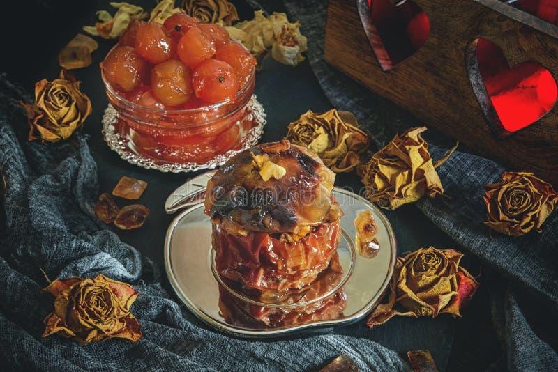 Apple cuit au four avec des écrous, le miel et Apple bloquent pour le thé sur le fond du bougeoir avec des coeurs photographie stock