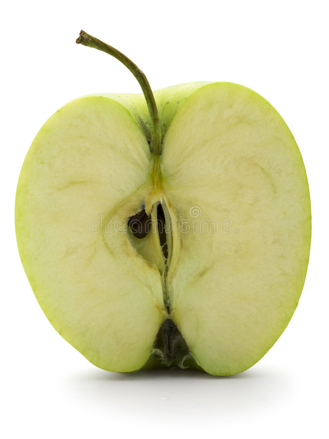 Apple cut in half. A green apple cut in half isolated on white background royalty free stock photo