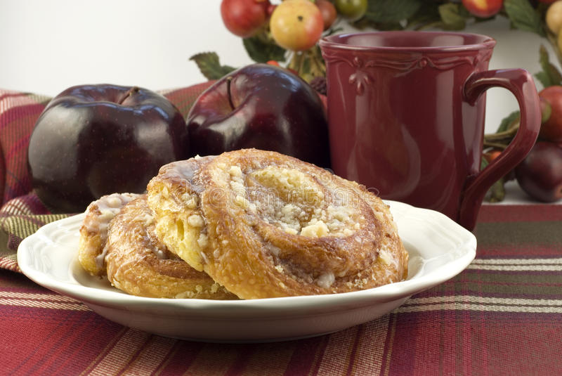 Apple Danish with Coffee. Apple danish on a plate with two red apples in the background and a cup of coffee, shallow depth of field, horizontal with copy space royalty free stock images