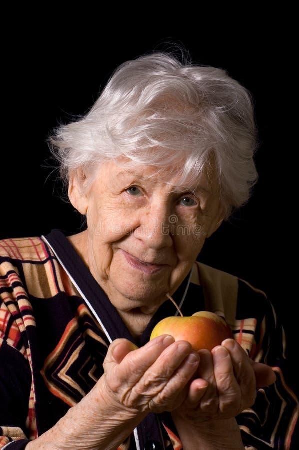 Apple dans une main de dame âgée images libres de droits