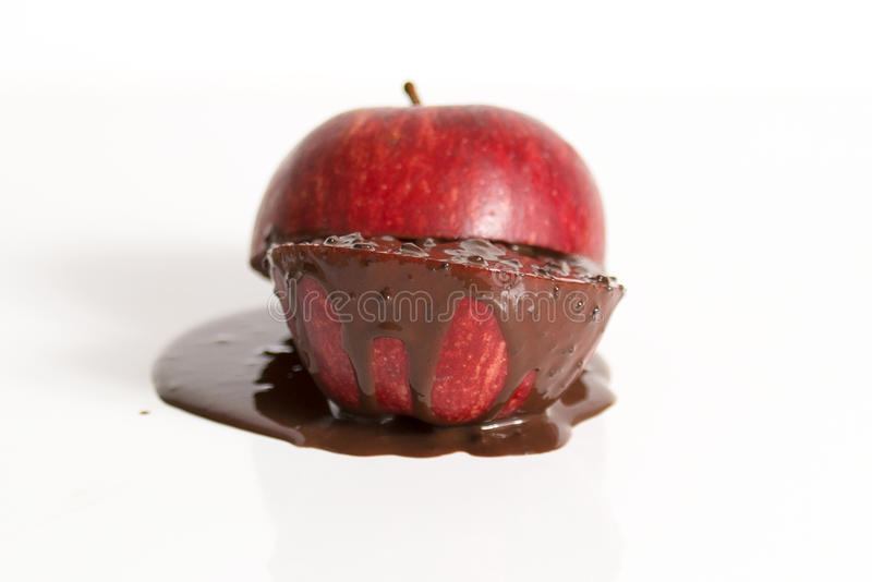 Apple with dark chocolate oozing out. stock photography