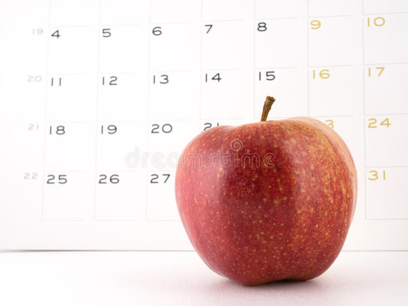 An apple a day. Close-up of an apple with a calendar on the background. Intended to illustrate a proverb 'An apple a day keeps the doctor away royalty free stock photography