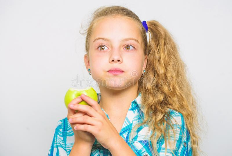 Apple a day keeps doctor away. Good nutrition is essential to good health. Kid girl eat green apple fruit. Nutritional. Content of apple. Vitamin nutrition stock photo