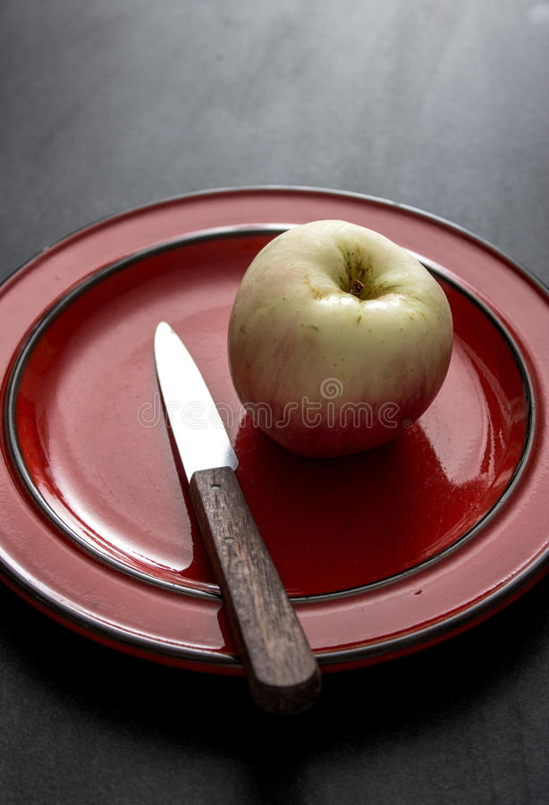 An apple a day. Single red and yellow apple sits on a plate with a knife,on a dark rustic table,selective focus stock images