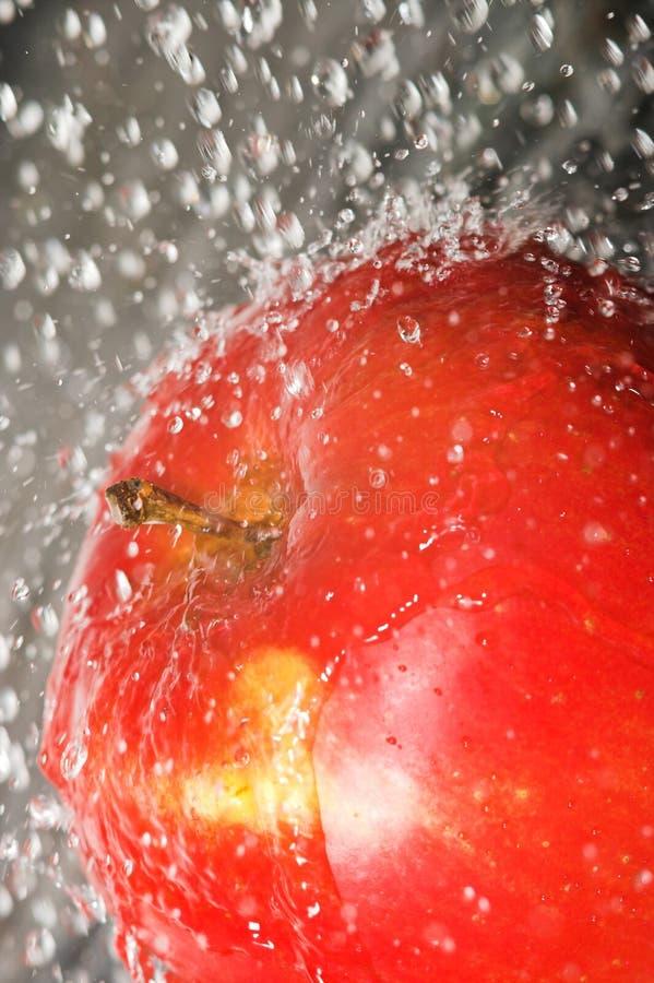 Apple, der Wasser spritzt lizenzfreie stockfotografie