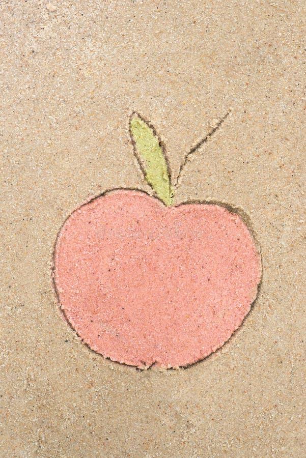Apple die in zand trekken royalty-vrije stock foto