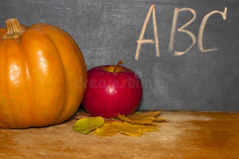 Apple e abóbora na tabela da sala de aula na frente do quadro-negro imagem de stock