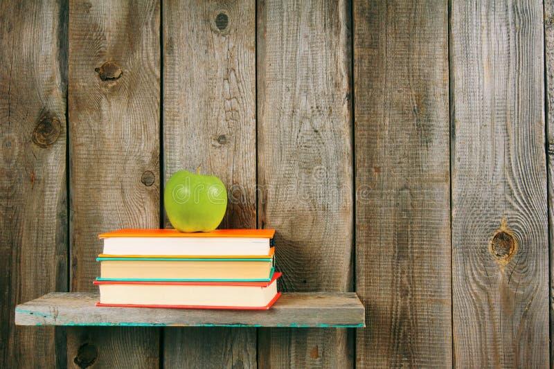 Apple e libri su uno scaffale di legno fotografia stock libera da diritti