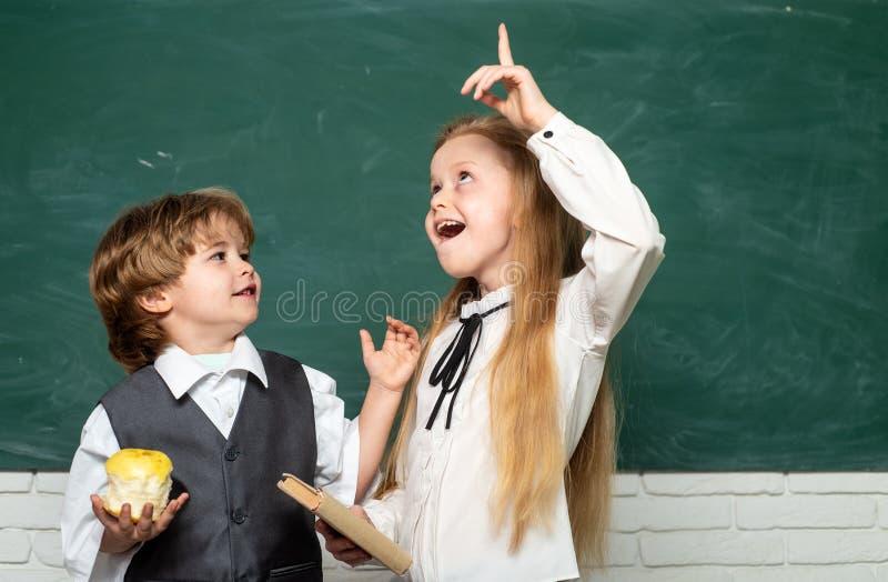 Apple e livros - conceito da escola Pares de estudante e de estudante no amor junto Escola das crian?as Processo educacional imagens de stock