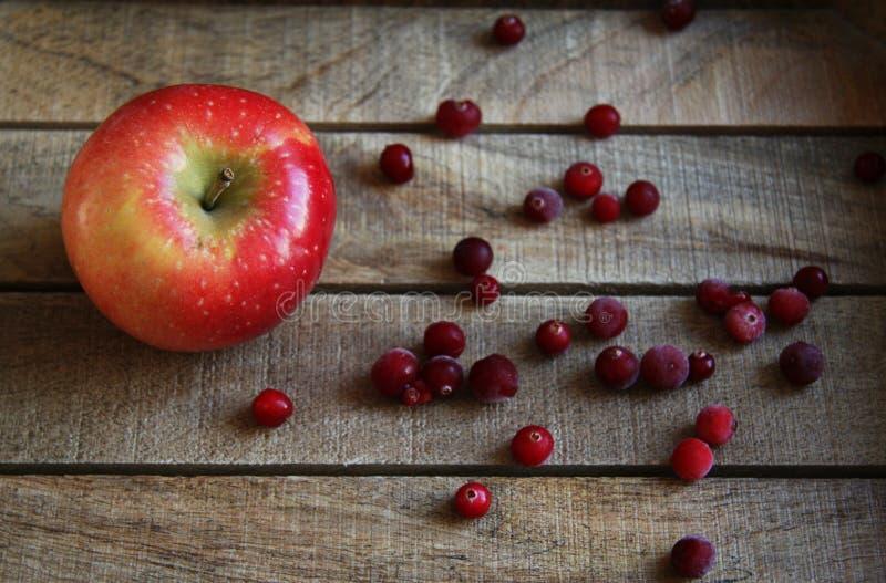 Apple e mirtilli rossi su una tavola di legno fotografie stock