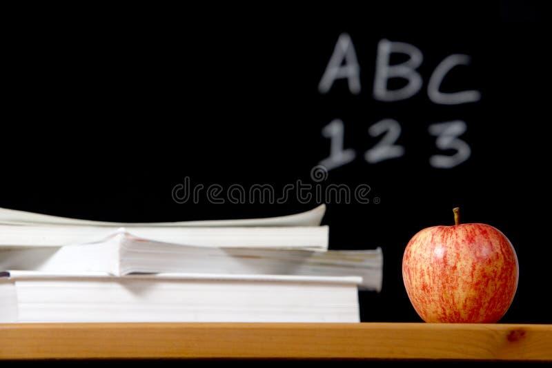 Apple e pila di libri in aula immagine stock