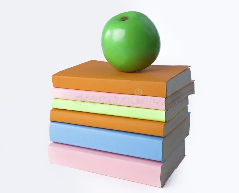 Apple e pila verdi di libri su fondo bianco Foto con lo spazio della copia immagini stock libere da diritti