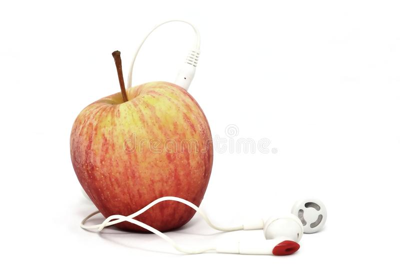 Apple with Earphones. A conceptual shot of an apple with earphones plugged into it stock photo
