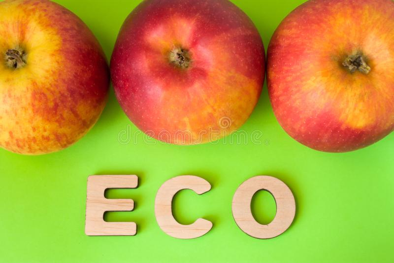 Apple Eco product or food. Three apples are on green background with text eco wooden letters. Example of sustainable environmental stock image