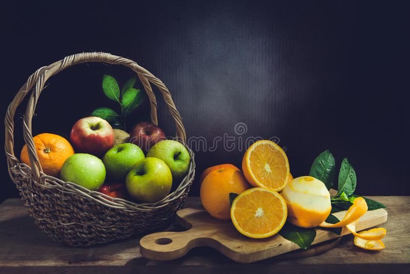 Apple is in een oranje mand op een houten scherpe raad stock foto's