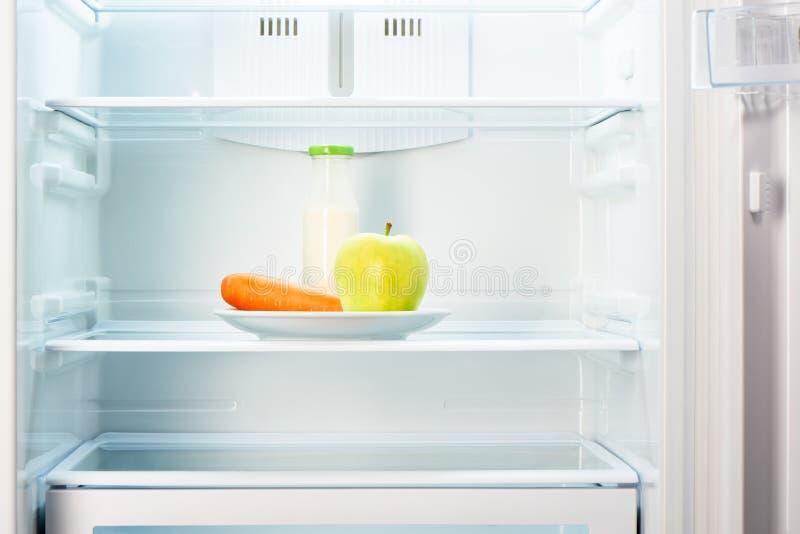 Apple en wortel met fles yoghurt in ijskast royalty-vrije stock foto's