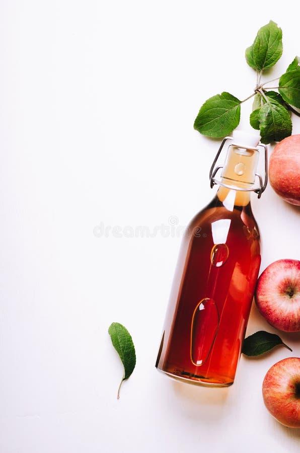 Apple-Essig in der Flasche auf weißem Holztisch mit Äpfeln und Blättern Rustikale Art Draufsicht, Kopienraum lizenzfreies stockfoto