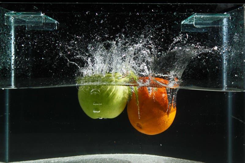 Apple et éclaboussement orange dans l'eau sur un fond noir photographie stock libre de droits