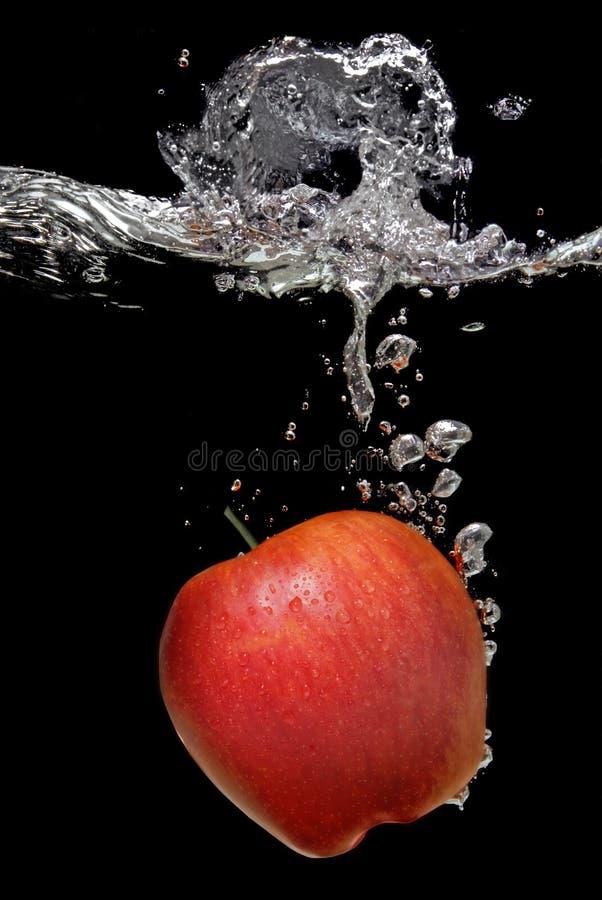 Apple fiel in Wasser mit Spritzen lizenzfreies stockbild