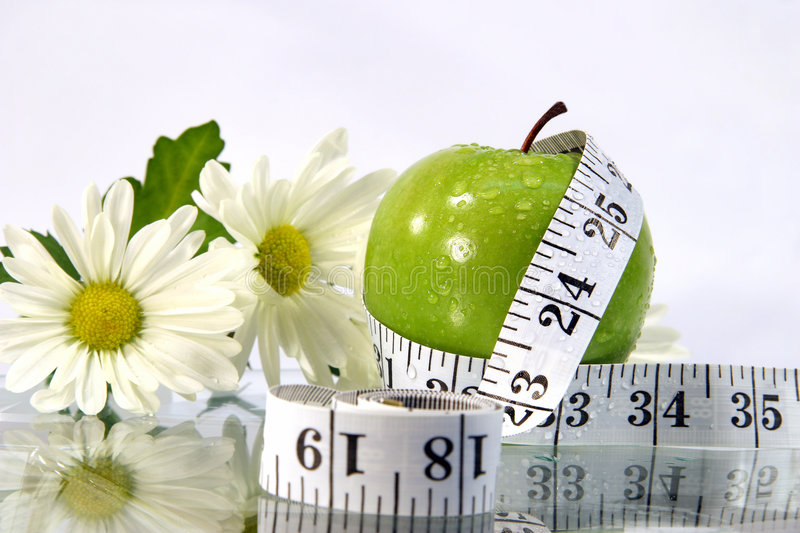 Apple, flowers and measurement tape. Measurement tape wrapped around green apple/Concept for health, diet royalty free stock image