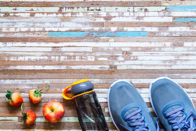 Apple, fresas, botella de agua y zapatillas deportivas en fondo de madera oxidado Fondo sano activo del concepto de la forma de v fotos de archivo