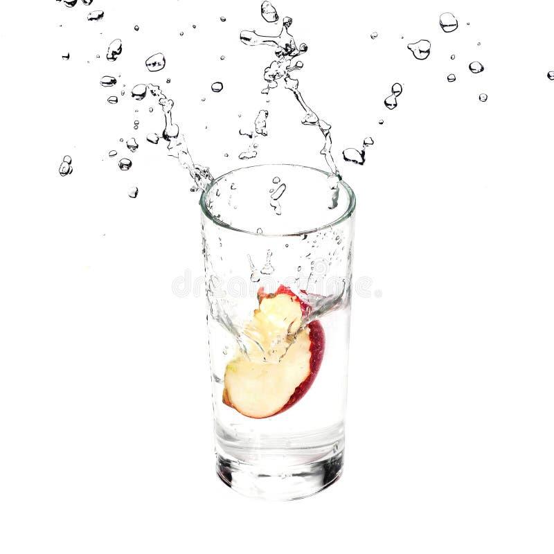 Apple fresco está espirrando no vidro com água pura isolada no fundo branco imagem de stock