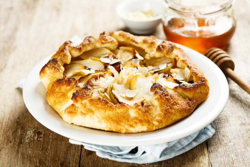 Apple galette with nuts and raisins. Homemade apple galette with raisins, almond and honey royalty free stock photo
