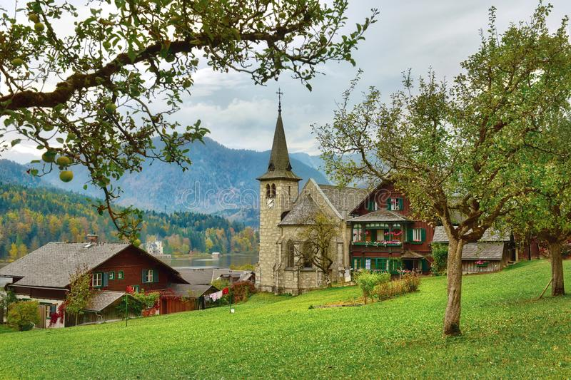 Apple garden in front of the old parish church on a cloudy autumn day. Grundlsee, Styria, Austria. Apple garden in front of the old parish church on a cloudy stock image