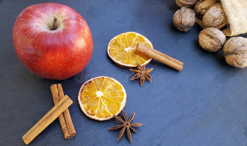 Apple, getrocknete orange Scheiben, Zimtstangen und Walnüsse stockfotos