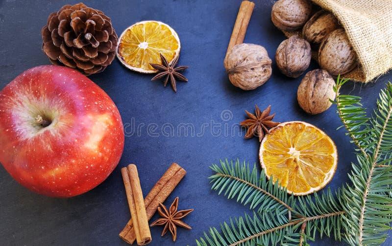 Apple, getrocknete orange Scheiben, Zimtstangen, Walnüsse und Weihnachtsbaum stockfotos
