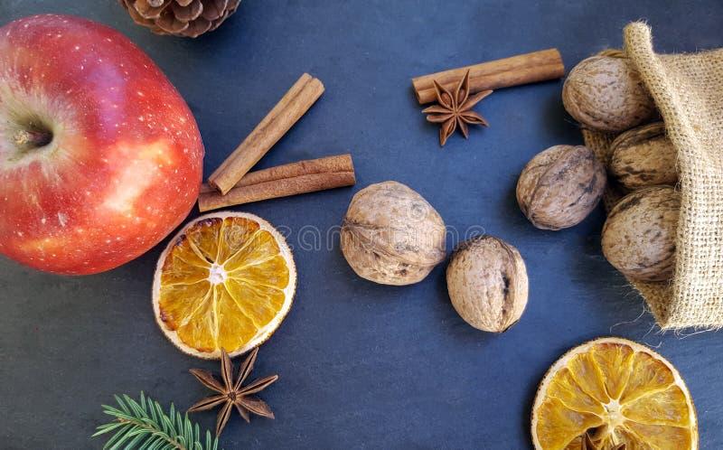 Apple, getrocknete orange Scheiben, Zimtstangen, Walnüsse und Weihnachtsbaum lizenzfreie stockfotos