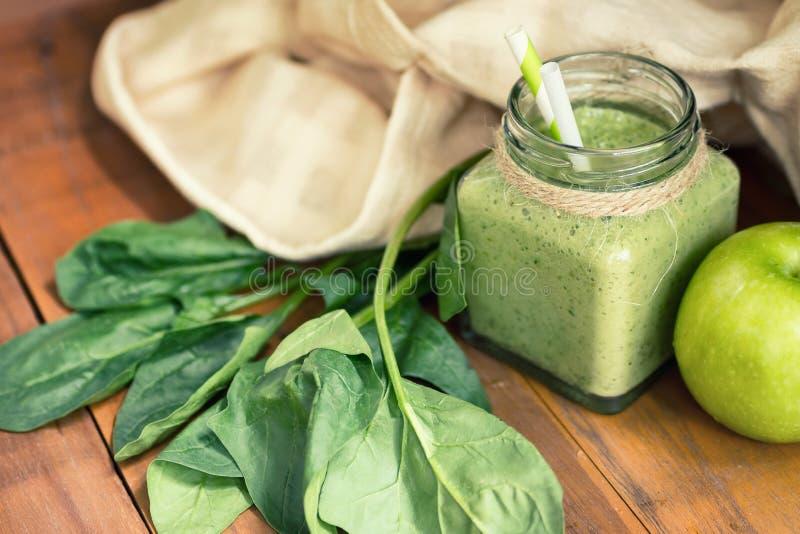 Apple - grön smoothie för spenat i murarekrus med ingredienser arkivbild