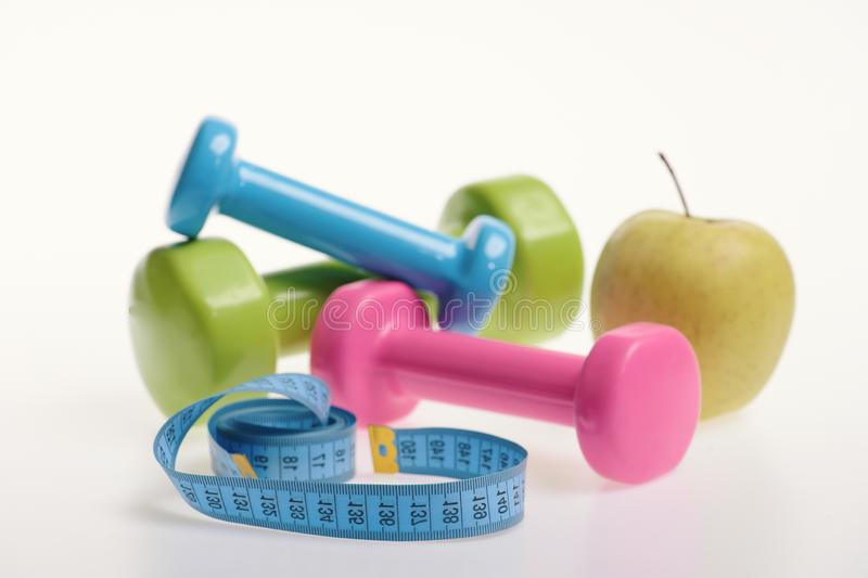 Apple and green, pink and blue barbells near measure tape royalty free stock photography