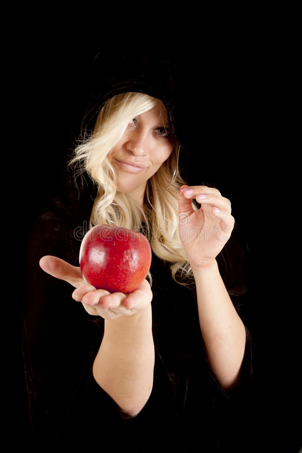 Apple hand. A woman holding out her happle while wearing a cloak with a sneaky smile on her face stock photography