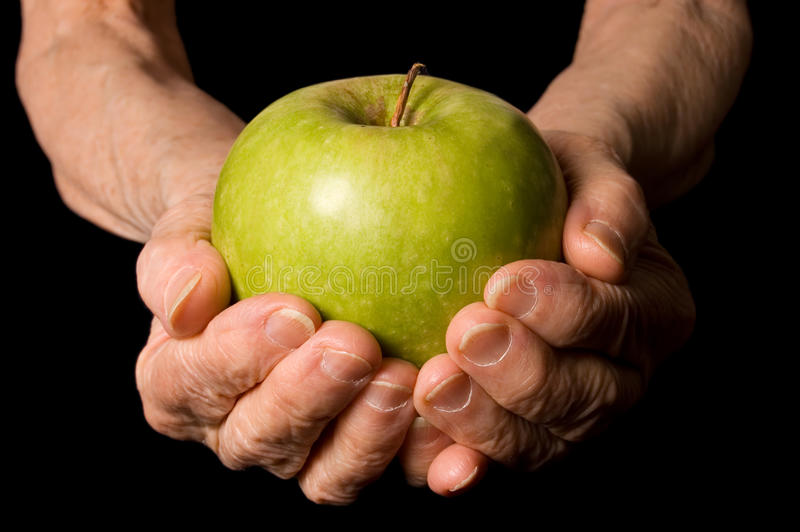 Apple in a hand of the old woman stock photos