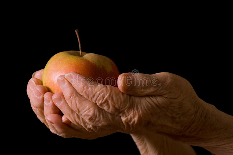 Apple in a hand of the old woman on the black royalty free stock photography