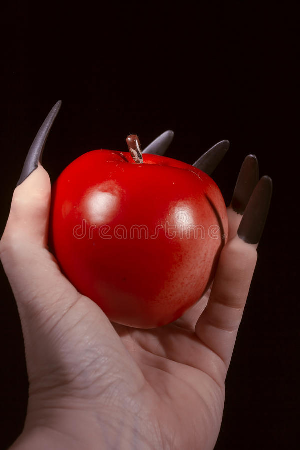 Apple in the hands with claws. Red apple in the hands of a witch royalty free stock photo