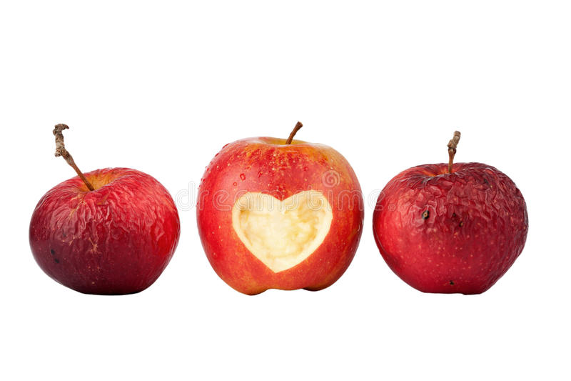 Apple with a heart symbol and two old apples. Isolated on white stock image